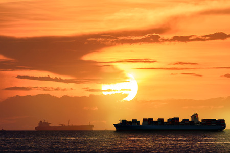 Logistics and transportation of International Container Cargo ship with tugboat in the ocean at sunset sky, Freight Transportation, Shipping