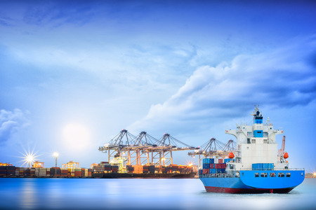 importation: Logistics and transportation of International Container Cargo ship with ports crane bridge in harbor for logistics import export background and transportation industry. Stock Photo
