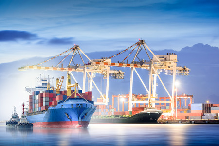 importation: Logistics and transportation of international container cargo ship with ports crane bridge in harbor at dusk for logistics import export background and transportation industry