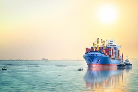 국제 컨테이너의 물류 및 운송 일몰 하늘,화물 운송, 해운에서 바다에 예인선이있는 화물선