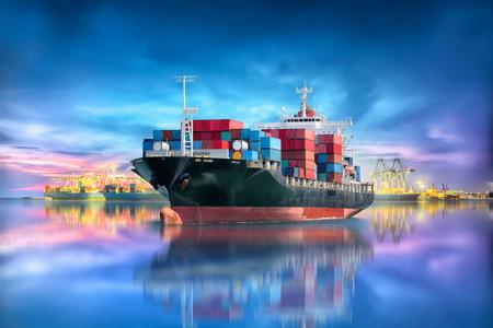Logistiek en vervoer van internationaal containervrachtschip met de brug van de havenkraan in zeehaven bij schemeringhemel voor de de uitvoer van de logistiekimport achtergrond en de vervoersindustrie Stockfoto