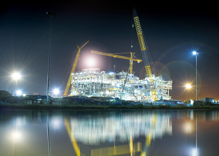 Construction of oil and gas refinery at night with water reflection