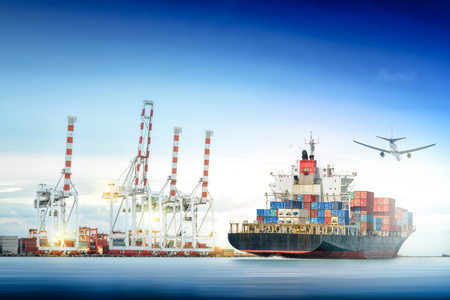 Logistics and transportation of Container Cargo ship and Cargo plane with working crane bridge in shipyard background, logistic import export background and transport industry. Stock Photo