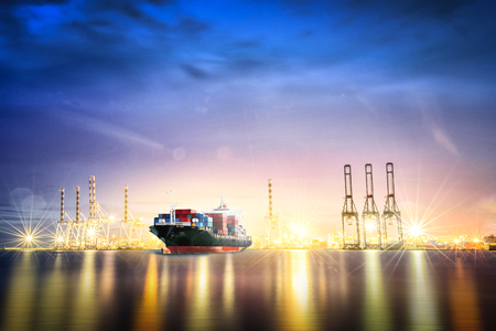 Logistics and transportation of International Container Cargo ship with ports crane bridge in harbor at Twilight sky for logistic import export background and transport industry.