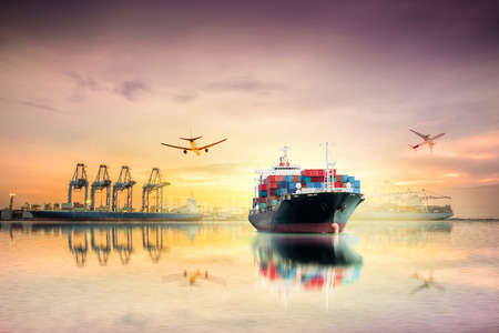 Logistics and transportation of International Container Cargo ship and Cargo plane with ports crane bridge in harbor at Twilight sky for logistic import export background and transport industry. Stock Photo