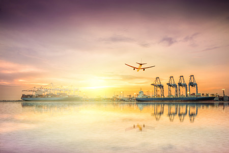Logistics and transportation of Container Cargo ship and Cargo plane with working crane bridge in shipyard at sunset sky, logistic import export background and transport industry