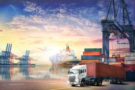 Logística de importación fondo exportación y la industria del transporte de camiones de contenedores y el buque de carga de trabajo con puente-grúa en el astillero en el cielo del atardecer