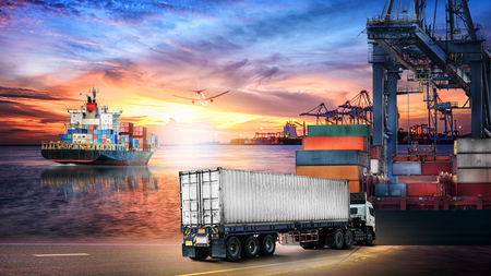 Logistics import export background and transport industry of Container truck and Cargo ship with working crane bridge in shipyard at sunset sky Foto de archivo