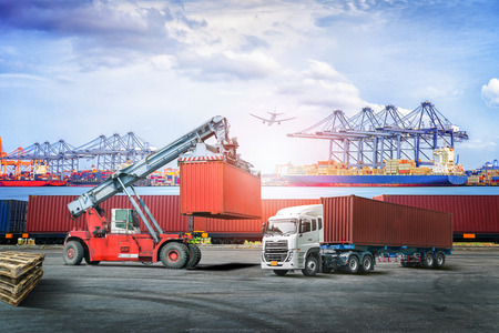 Logistics import export background and transport industry of forklift handling container box loading at seaport Stockfoto