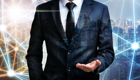 Double exposure, business man holding something imaginary on palm of his hand at city night background, internet of things and advertisement concept, hand focus