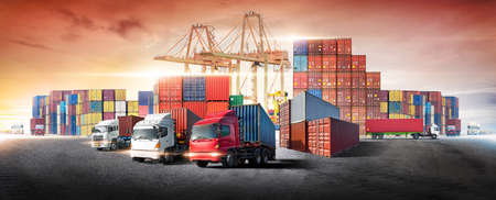 Business logistics and transportation concept of containers box from cargo freight ship with working crane bridge in shipyard at sunset sky, logistic import export and transport industry background