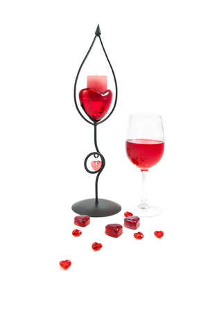 A wineglass with a candle and hearts Stock Photo