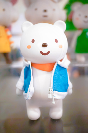 BANGKOK - MAY 7, 2016 : Portrait shot of Ordinary Bear vinyl mascot wearing orange scarf and his casual blue jacket along with other friends on the background. Character designed by Fluffy House.