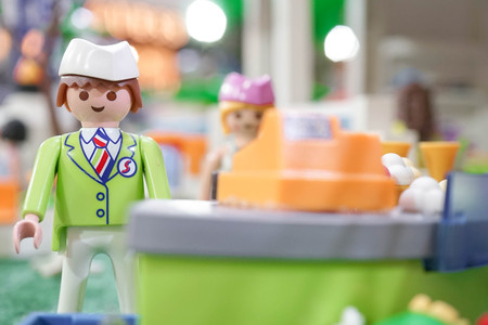 BANGKOK - MAY 6, 2016 : Portrait shot of Playmobil Shop assistant in green uniform standing behind the cashier. Customer service. Playmobil belongs to a toy company, the Brandstatter Group, in Germany Sajtókép