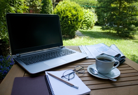 Laptop and coffee on a table in garden, outdoor work During a coffee break, notebook and magazine on a wooden table Stock fotó