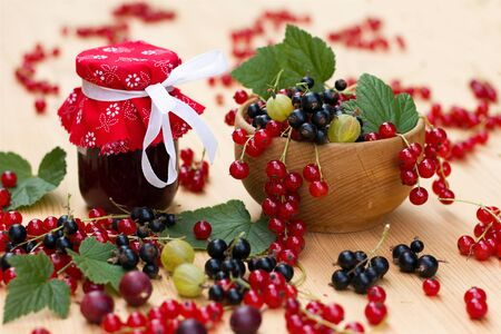 Black, red currants and Gooseberries in a wooden bowl, scattered small organic fruit and glass of jam on a wooden table