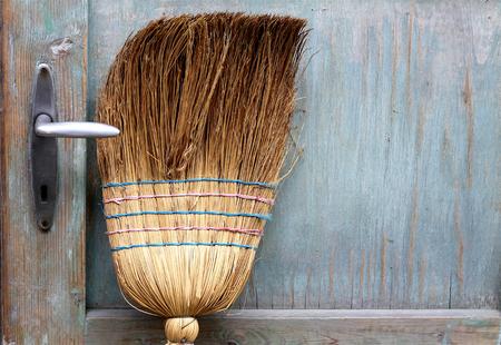 Broom leaning on an old door