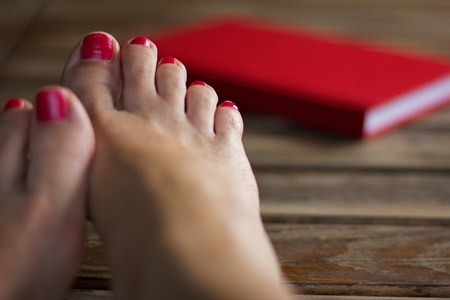 toenails: Bare feet on the desk of a young woman, red painted toenails, woman relaxing with a book Stock Photo