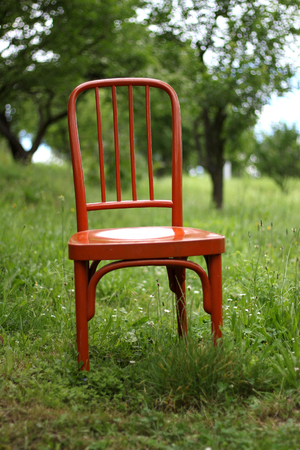 Empty wooden retro red chair in the garden, an old chair