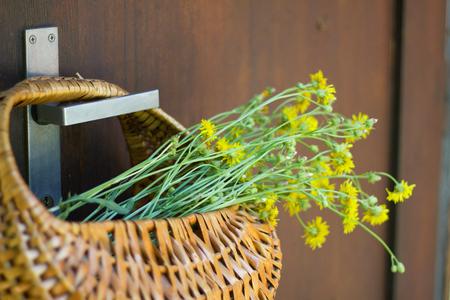Wicker basket with wildflowers hanging on the metal handle, wooden door