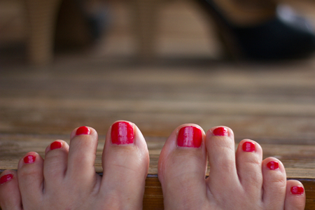 toenails: Bare feet on the desk of a young woman, red painted toenails, woman relaxing