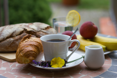 banana bread: Breakfast with cup of coffee and a croissant, bread and fruits in background