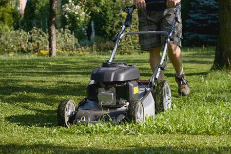 Man cutting grass the lawn mower, powerful petrol lawn mower in sunlight