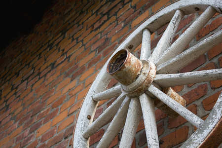 Vintage old wheel from the vehicle hanging on the wall, brick wall as background