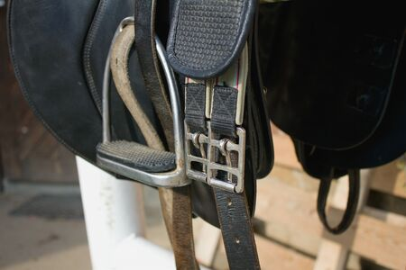 stirrup: Black leather on a barrier in the stable, and Stirrup buckle in detail