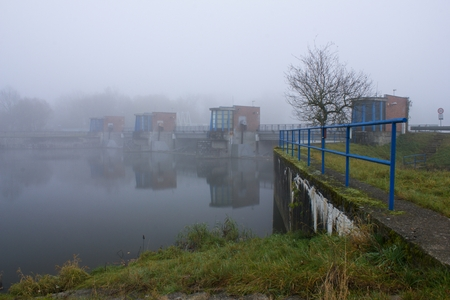 Old water dam on the river in the morning mist. Autumn fog over the river weir.