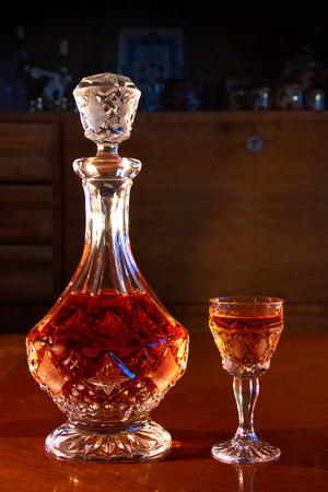 crystal decanter and glasses full of rum, carafe and a dram of alcohol on a wooden table, dark living room with antique furniture as background Stock fotó