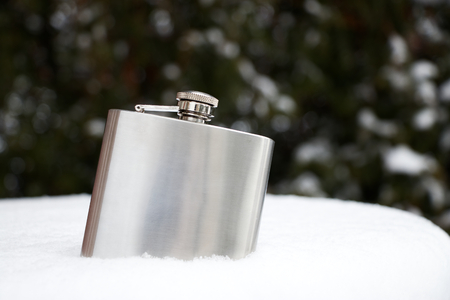 metal hip flask in snow, plate silver flask for alcohol at winter season