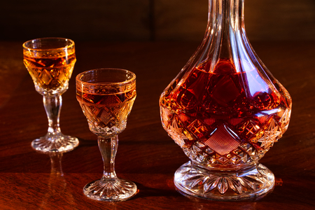crystal decanter and glasses full of rum, carafe and a dram of alcohol on a wooden table, dark background Stock Photo
