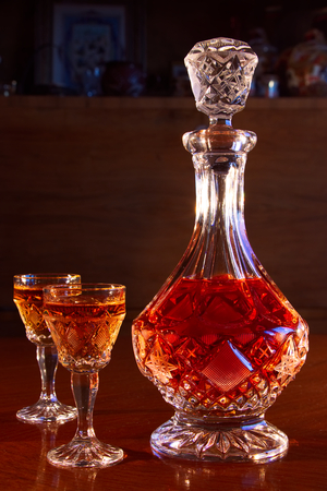 crystal decanter and glasses full of rum, carafe and a dram of alcohol on a wooden table, dark living room with antique furniture as background Stock Photo