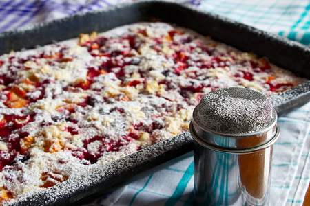 fruitcake and metal sugar bowl on wooden table, sugared fruit pie on baking tray, kitchen towels