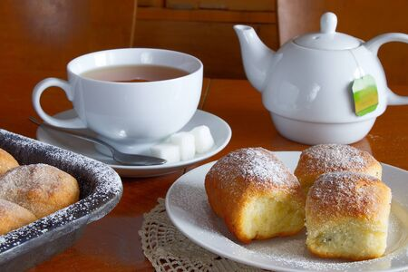 Sugared poppy seed buns on a plate with a cup of tea and porcelain pot on a wooden table. A sweet breakfast with lace placemats.
