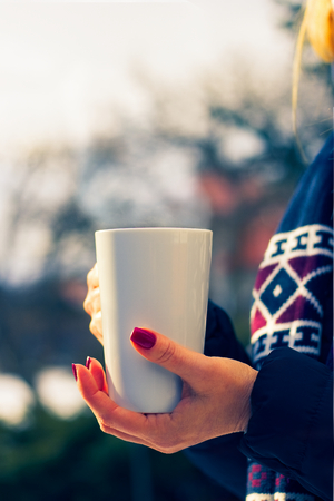 woman holding a steaming hot cup of coffee in her hands outdoors in winter, numbed female hands with polished nails, cool toned