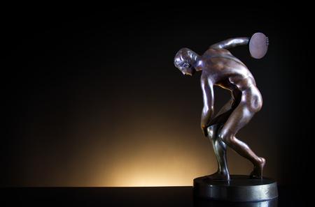 discus: discobolus bronze on dark gradient background, antique banner, a symbol of the ancient sport discus throw Stock Photo