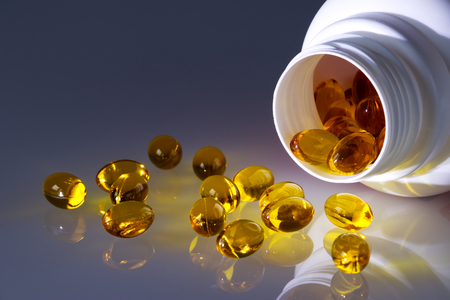 Omega 3 fish oil capsules spilled from a plastic bottle on a gradient background. Medical food supplements. Unsaturated fatty acid Stock Photo