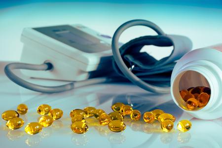 fish oil omega 3 capsules for prevention against hypertension, equipment for measuring blood pressure in the background, tablets spilled from plastic bottle