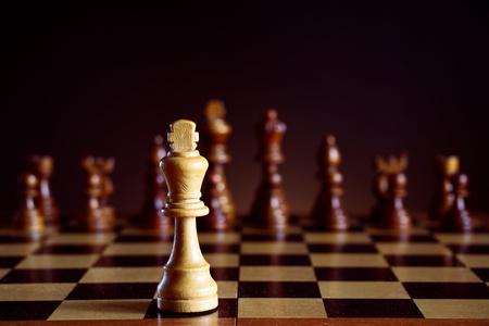 Weißer Schachkönig vor einem Schachbrett, schwarze Schachfiguren auf einem dunklen Hintergrund Standard-Bild - 73420086