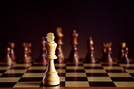 White chess king in front of a chessboard, black chess pieces on a dark background