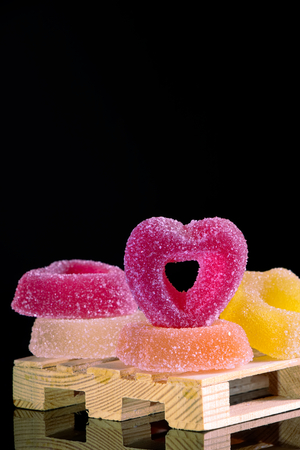 colored jelly candies on a black background, sugared sweets with large copy space