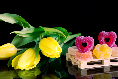 poetic: Romantic sugared sweets and a bouquet of yellow tulips, jelly candies with flowers as a gift on a black background