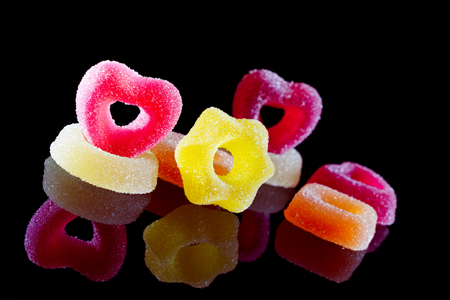 colored jelly candies on a black background, sugared sweets