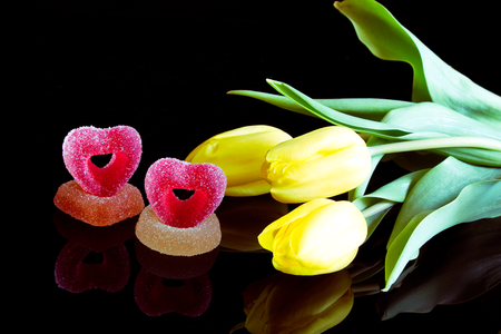 Romantic sugared sweets and a bouquet of yellow tulips, jelly candies with flowers as a gift on a black background