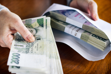 bribes: Money in an envelope as a symbol of corruption. Taking bribes, Czech currency in criminal activity. Woman inserts financial bribe in an envelope.