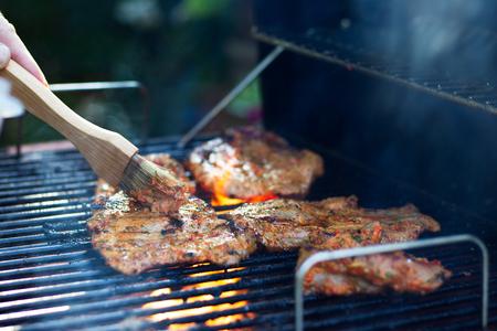 굽고있는 동안 고기를 marinating. 그릴에 돼지 고기. 정원에서 바베큐 파티. 모션에서 브러쉬 손으로입니다.
