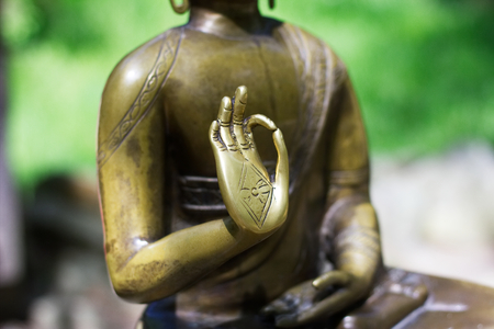 tantra: Hand of Buddha. A symbol of meditation and asian buddhist religion. Bronze statue of Buddha.