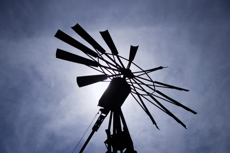 molino de agua: Windmill silhouette against the sun. An old way of pumping water through a windmill.